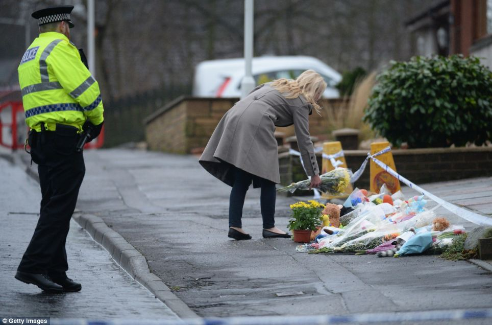 Tribute: A woman lays flowers at the scene where the three-year-old was found