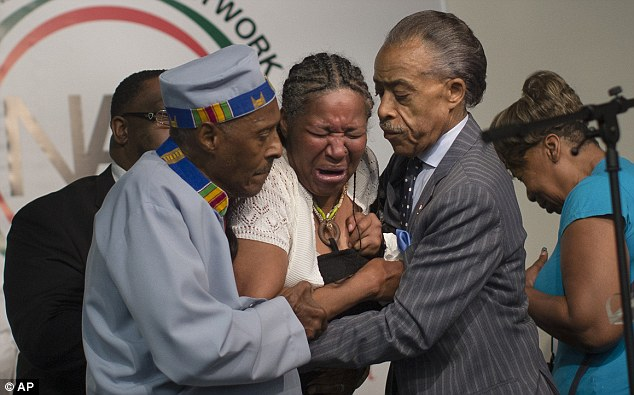 Traumatic: Esaw Garner, whose husband Eric died during an arrest Thursday, is held by the Rev Al Sharpton, right, and Rev Herbert Daughtry, on Saturday