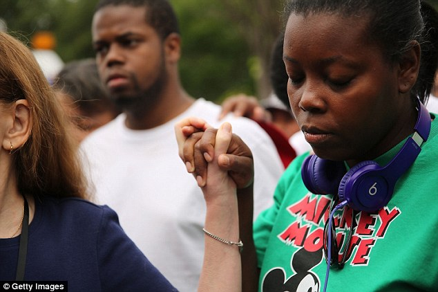 Members of the community join in prayer during a demonstration on Saturday over Garner's death