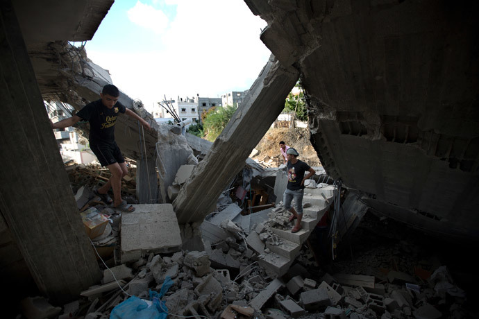 Palestinians inspect a destroyed building following an Israeli military strike on Beit Lahya, northern Gaza Strip on July 15, 2014. (AFP Photo / Mahmud Hams)